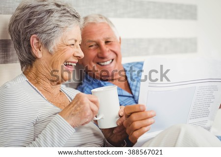 Senior couple laughing while reading newspaper in bedroom - stock photo