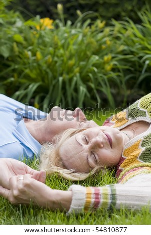 Senior couple laying on grass