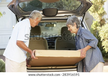 Senior Couple Loading Large Package Into Back Of Car - stock photo
