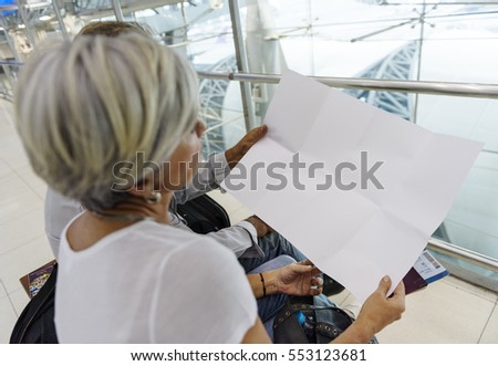 Senior couple looking at blank paper airport