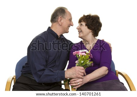 Senior Couple Looking At Each Other Holding Bouquet Over White Background - stock photo