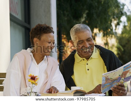Senior couple looking at map while sitting at table - stock photo