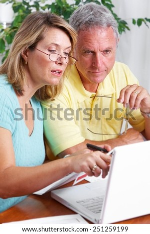 Senior couple looking bills at home with computer. - stock photo