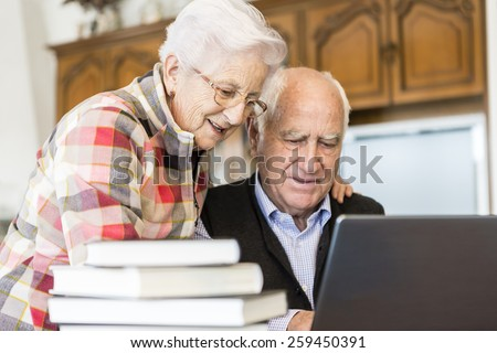 Senior couple looking for information in books and internet - stock photo