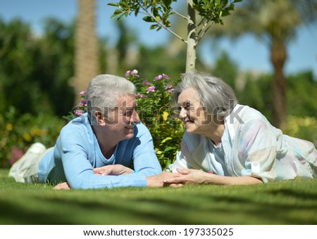 Senior couple lying on grass at hotel resort