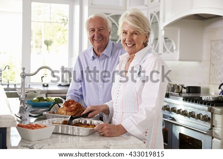 Senior Couple Make Roast Turkey Meal In Kitchen Together - stock photo