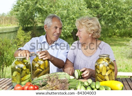 Senior couple making home made pickles - stock photo