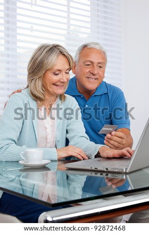 Senior couple making online purchases - stock photo