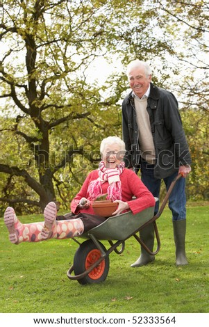 Senior Couple Man Giving Woman Ride In Wheelbarrow - stock photo