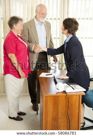 Senior couple meet loan officer to fill out application. - stock photo