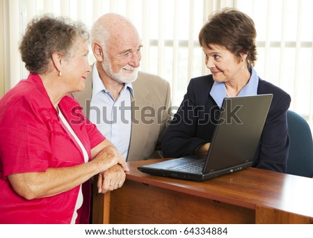 Senior couple meet with a sales woman or financial consultant. - stock photo