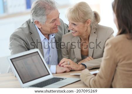 Senior couple meeting financial adviser in office - stock photo