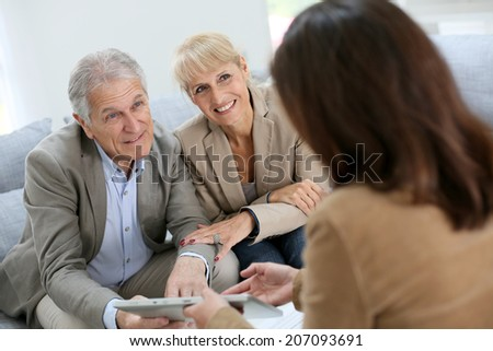 Senior couple meeting real estate agent - stock photo