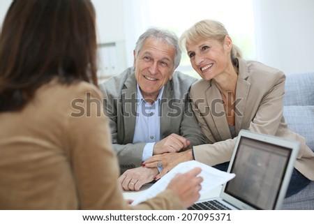 Senior couple meeting real estate agent - stock photo