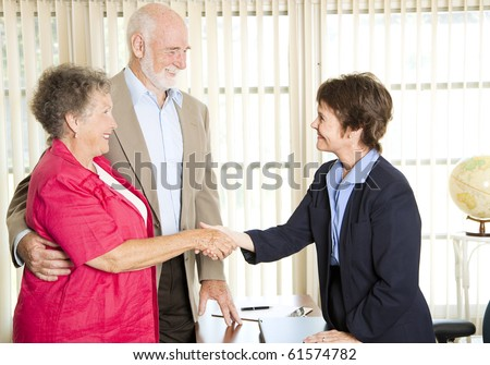 Senior couple meets with a friendly financial adviser. - stock photo