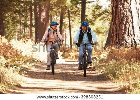 Senior couple mountain biking on forest trail, California - stock photo