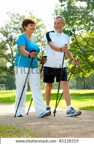 senior couple nordic walking in the park - stock photo