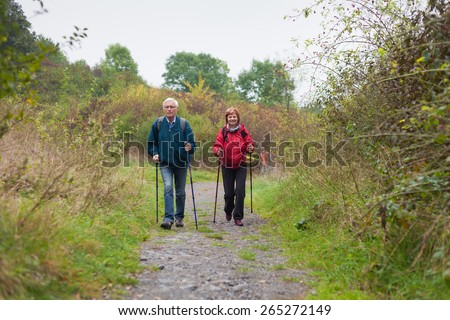 Senior couple Nordic walking on rocky trail in the nature. - stock photo