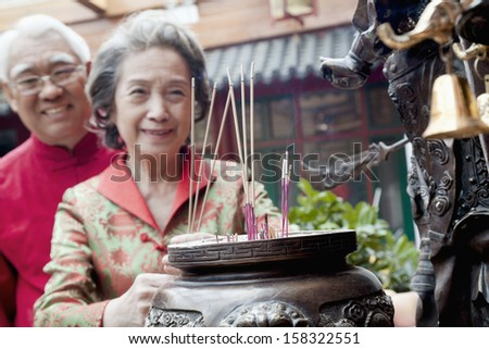 Senior couple offering incense at the temple in Beijing - stock photo