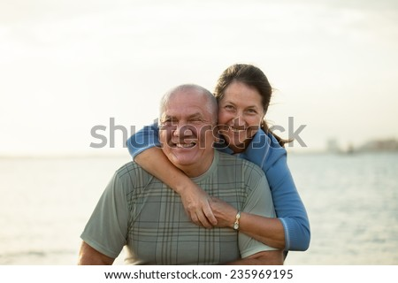 Senior couple on  beach in  sunset rays of  sun. - stock photo