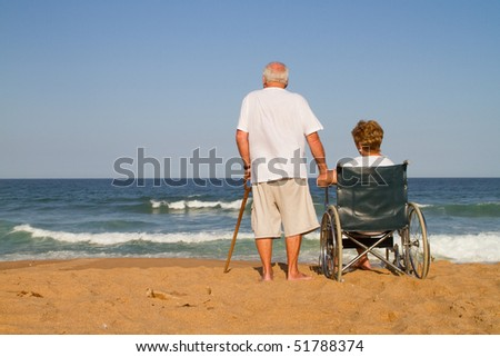 senior couple on beach, the wife is disabled and sitting on wheelchair - stock photo