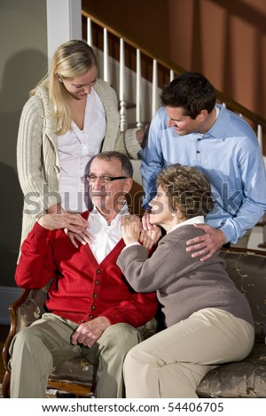 Senior couple on couch at home with adult children - stock photo