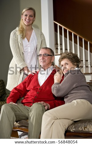Senior couple on couch at home with adult daughter