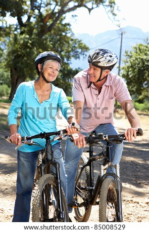Senior couple on country bike ride - stock photo