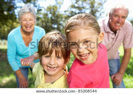 Senior couple on country walk with grandchildren - stock photo