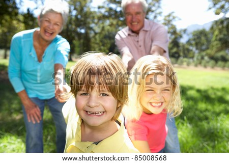 Senior couple on country walk with grandchildren - stock photo