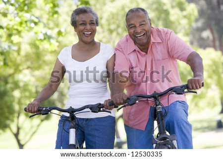 Senior couple on cycle ride in countryside - stock photo