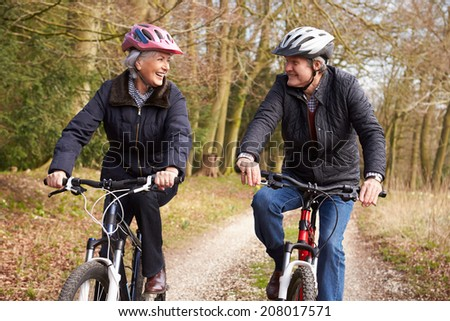 Senior Couple On Cycle Ride In Winter Countryside - stock photo