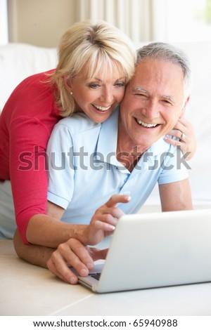 Senior couple on her laptop computer - stock photo