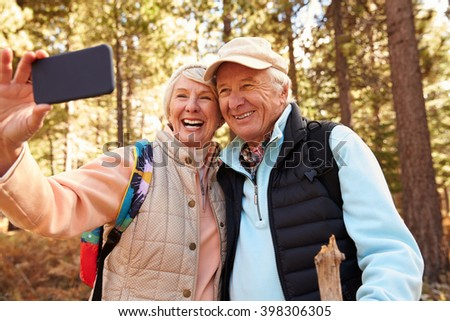 Senior couple on hike in a forest taking a selfie - stock photo