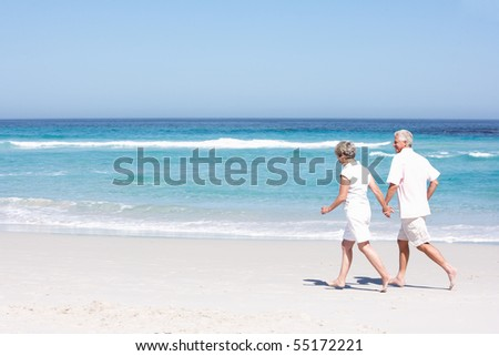 Senior Couple On Holiday Running Along Sandy Beach