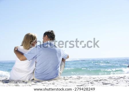 Senior Couple On Holiday Sitting On Sandy Beach - stock photo