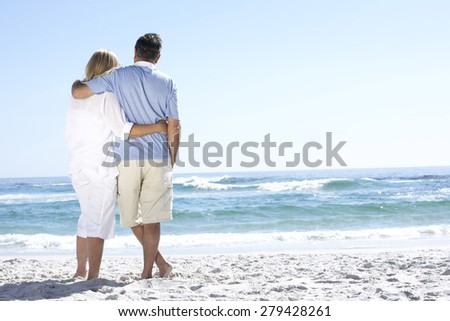 Senior Couple On Holiday Walking Along Sandy Beach Looking Out To Sea - stock photo
