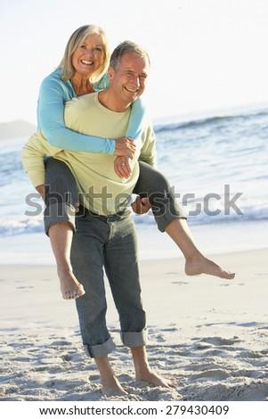 Senior Couple On Holiday With Husband Giving Wife Piggyback - stock photo