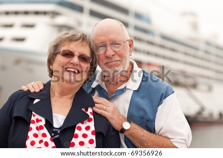 Senior Couple On Shore in Front of Cruise Ship While on Vacation. - stock photo