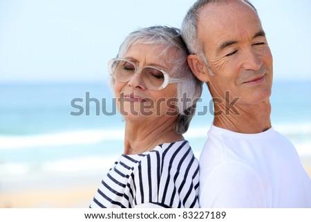 senior couple on the beach - stock photo