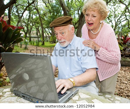 Senior couple on the internet reading a very funny e-mail. - stock photo