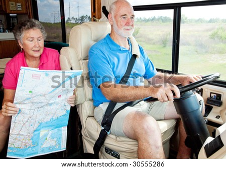 Senior couple on vacation in their motor home.  The wife is reading the map to her husband. - stock photo