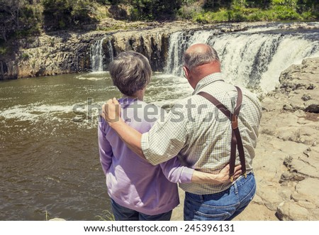 Senior Couple on vacation together looking at a waterfall