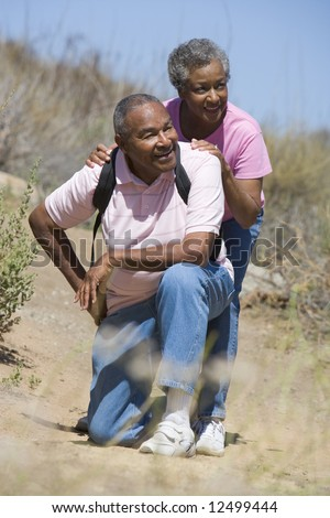 Senior couple on walk in countryside - stock photo