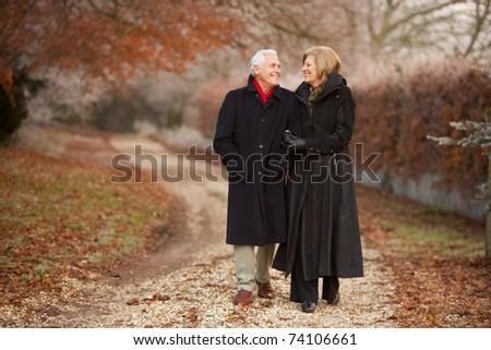 Senior Couple On Winter Walk Through Frosty Landscape - stock photo