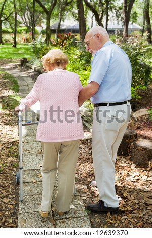 Senior couple out for a walk.  The husband is helping his wife with her walker. - stock photo