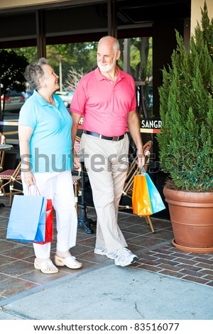 "Senior couple out shopping together.  (word visible in window is just ""sangria"", not restaurant name or logo) - stock photo"