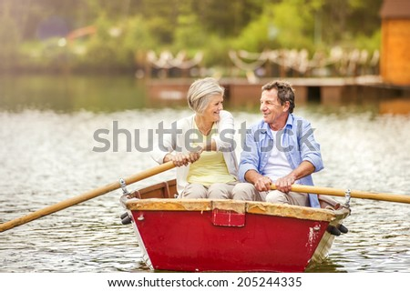 Senior couple paddling on boat on mountain tarn - stock photo