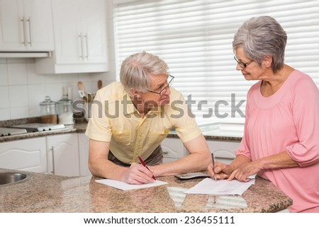 Senior couple paying their bills at home in the kitchen - stock photo