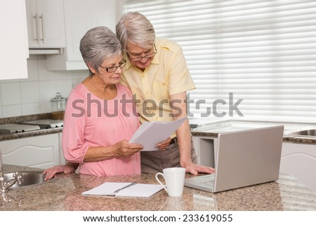 Senior couple paying their bills with laptop at home in the kitchen - stock photo